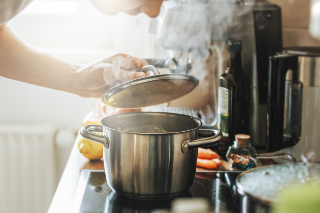 young-man-cooking-fresh-food-home-opening-lid-steaming-pot_1220-5351